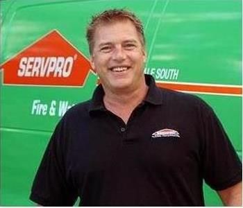 photo of male employee David facing forward with green truck in background