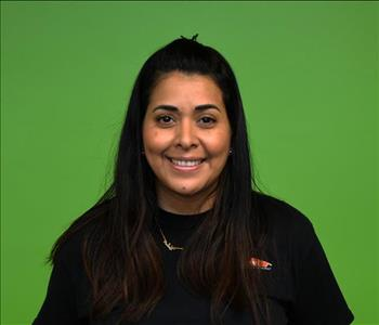 female employee, green background, wearing a black jacket and shirt