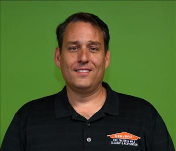 male employee posing in a black servpro shirt, green background