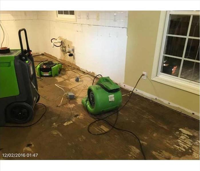 Wood subfloor being dried by SERVPRO green equipment