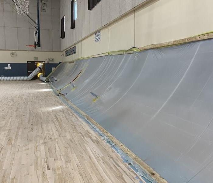 A gym with plastic sheeting covering bleachers.