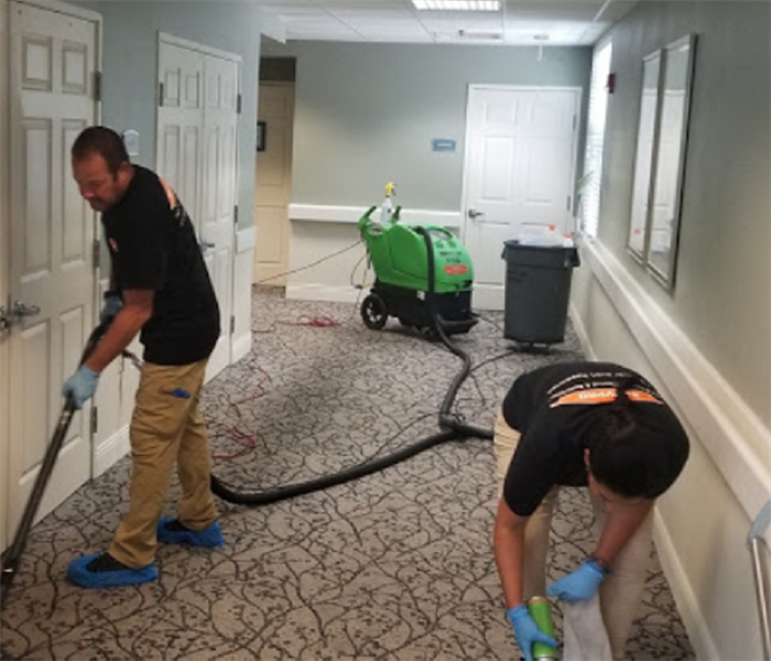 Two men removing water from business floor