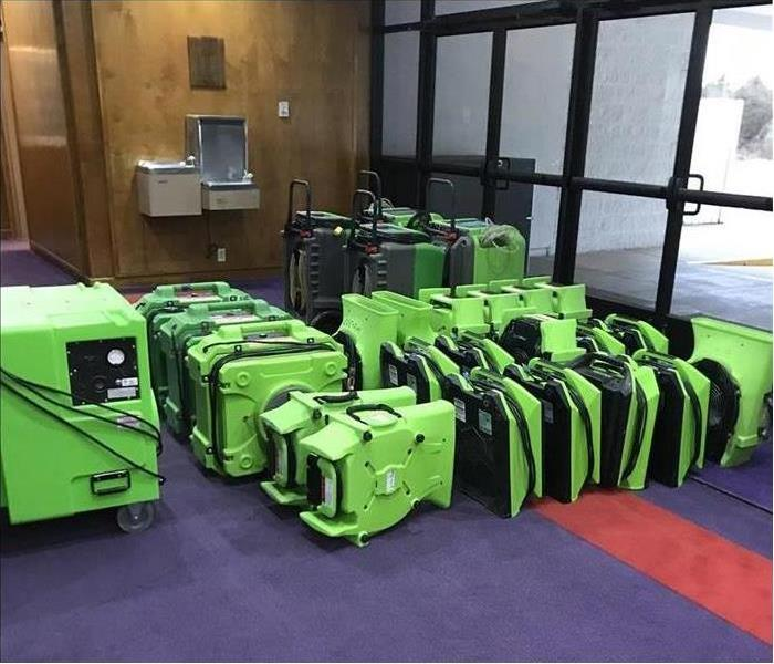 rows of SERVPRO fans and dehumidifiers sitting in the lobby of an office