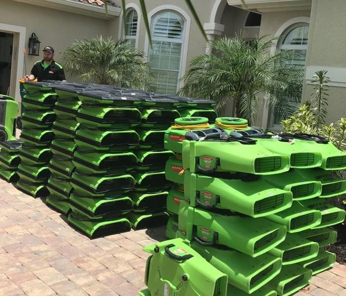 SERVPRO equipment stacked outside of a home